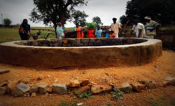 A wall was constructed around the well with stone, cement and sand and hard soil was added around it to stop the rain water from entering inside.