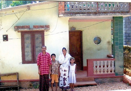 Mrs. Sheela and family in front of their home